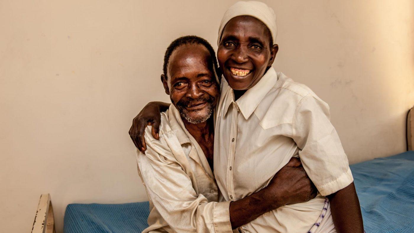 Un uomo e una donna di mezza età sorridono abbracciati.