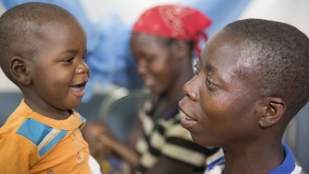 Una donna di profilo guarda un bambino di fronte a lei che sorride