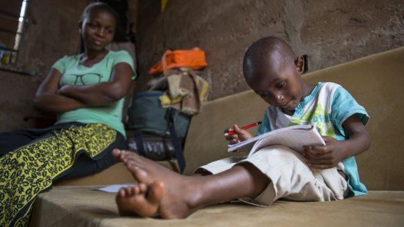 Baraka ha in mano una penna rossa e un quaderno e sta leggendo. Dietro di lui lo osserva la sua mamma.