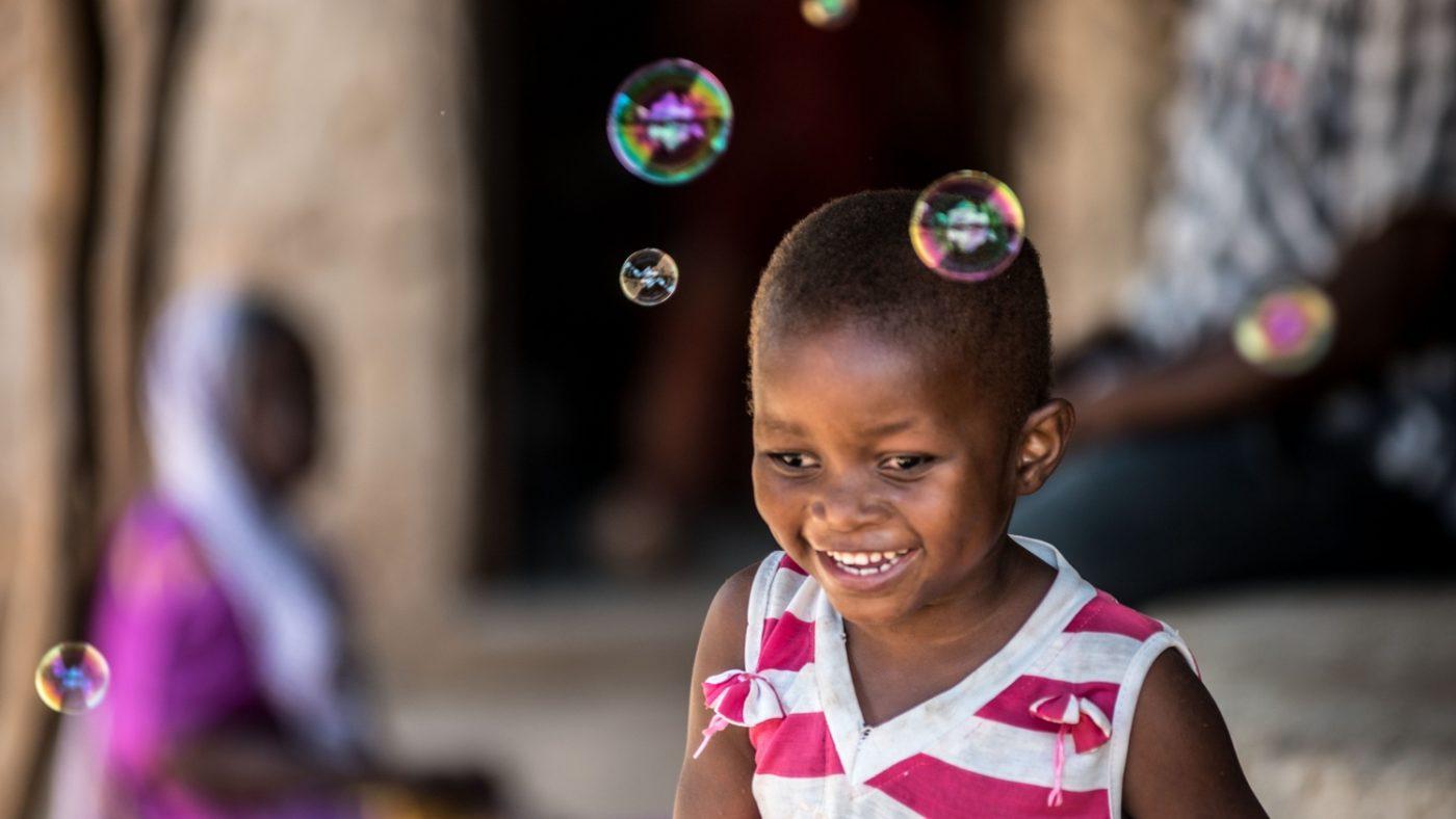 Una bambina sorride mentre gioca con le bolle di sapone