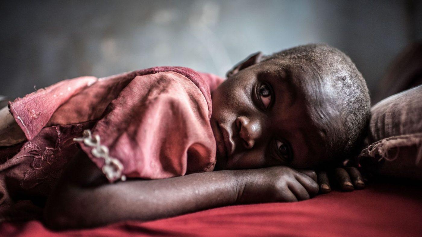Una bambina è sdraiata sul letto e ha gli occhi tristi