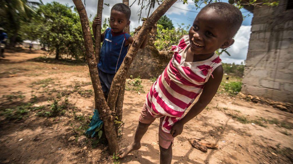 Due bambini sorridono in mezzo a degli alberi