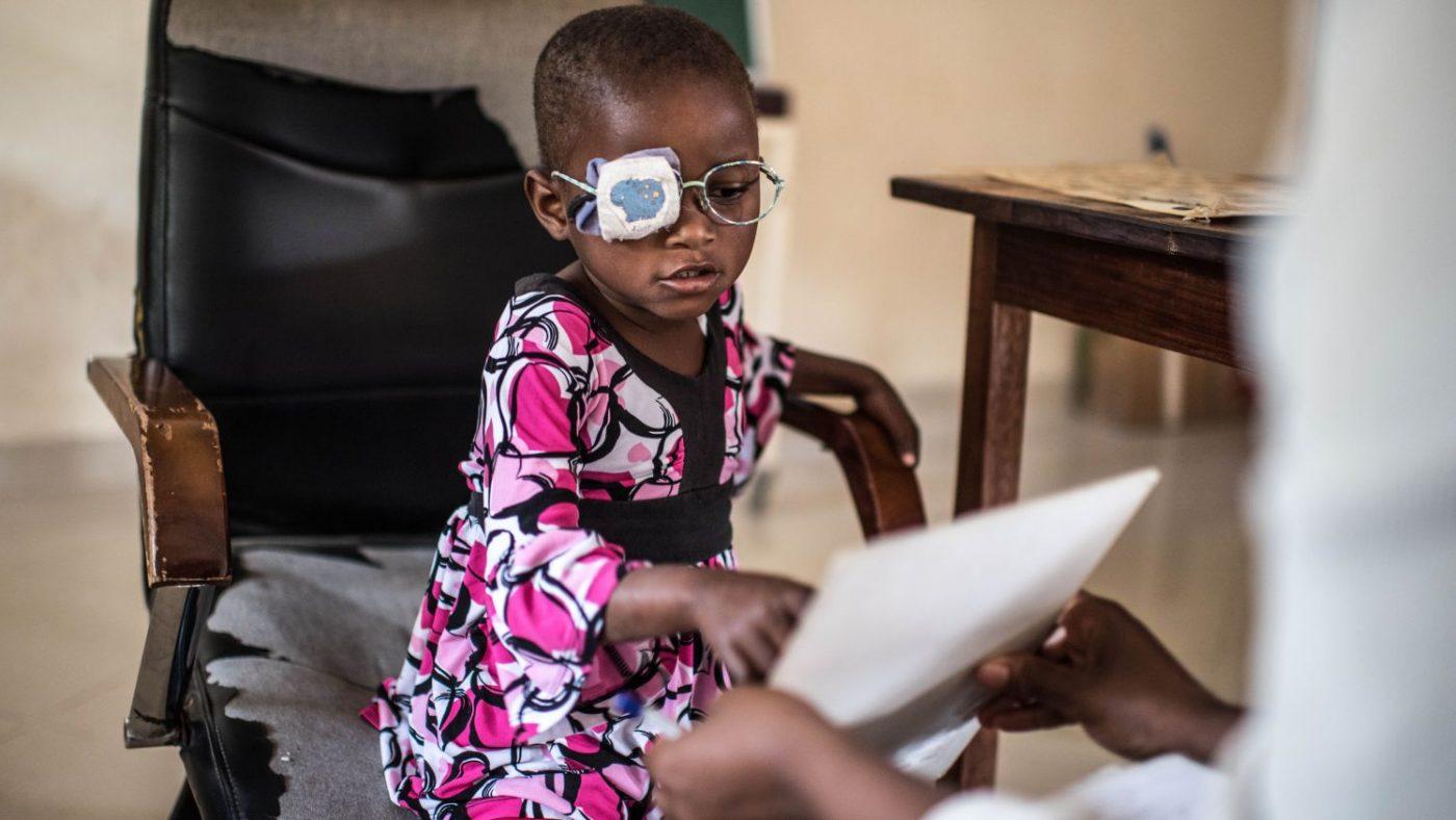Una bambina con la benda sull'occhio sinistro e gli occhiali da vista indica un foglio tenuto in mano da una donna di spalle
