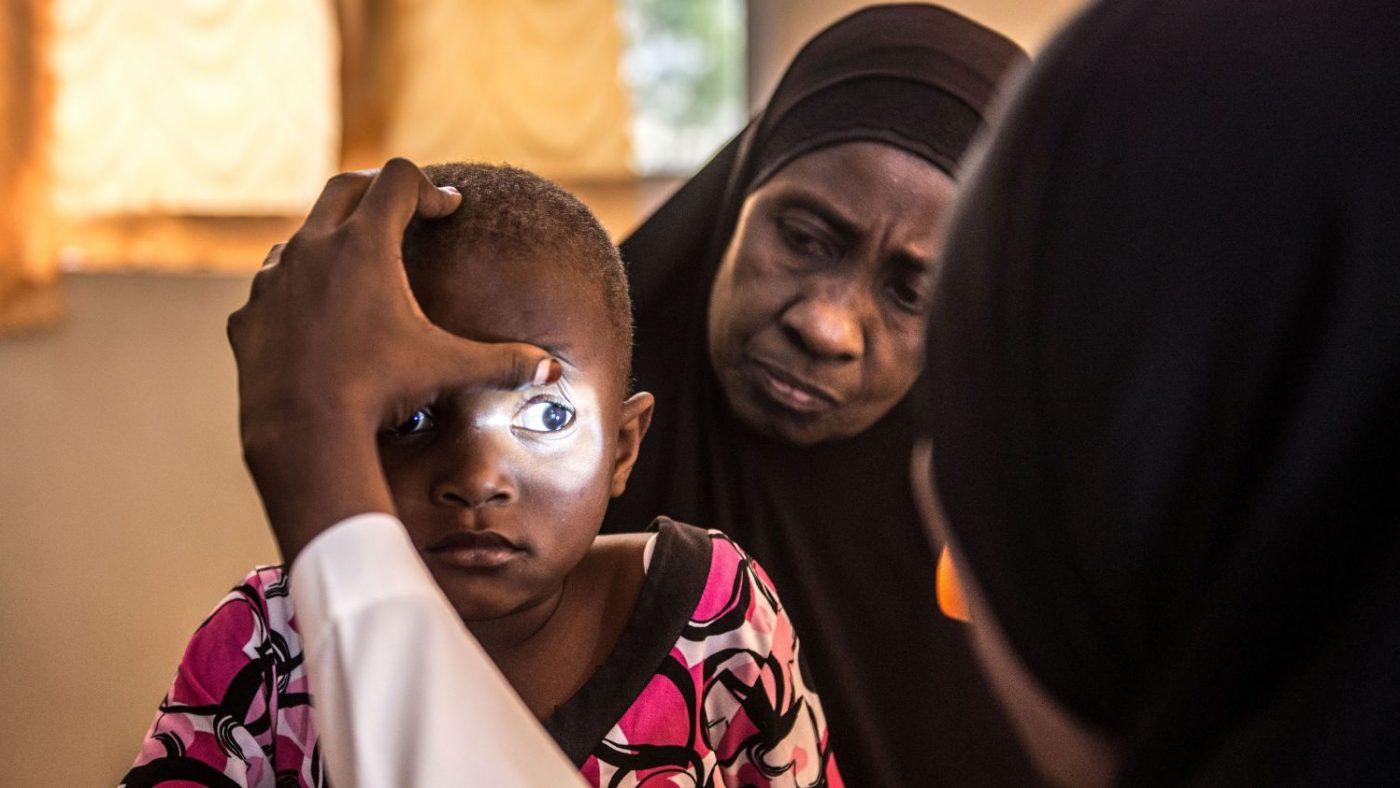 Un dottore visita gli occhi di Asha puntandole una luce sull'occhio destro
