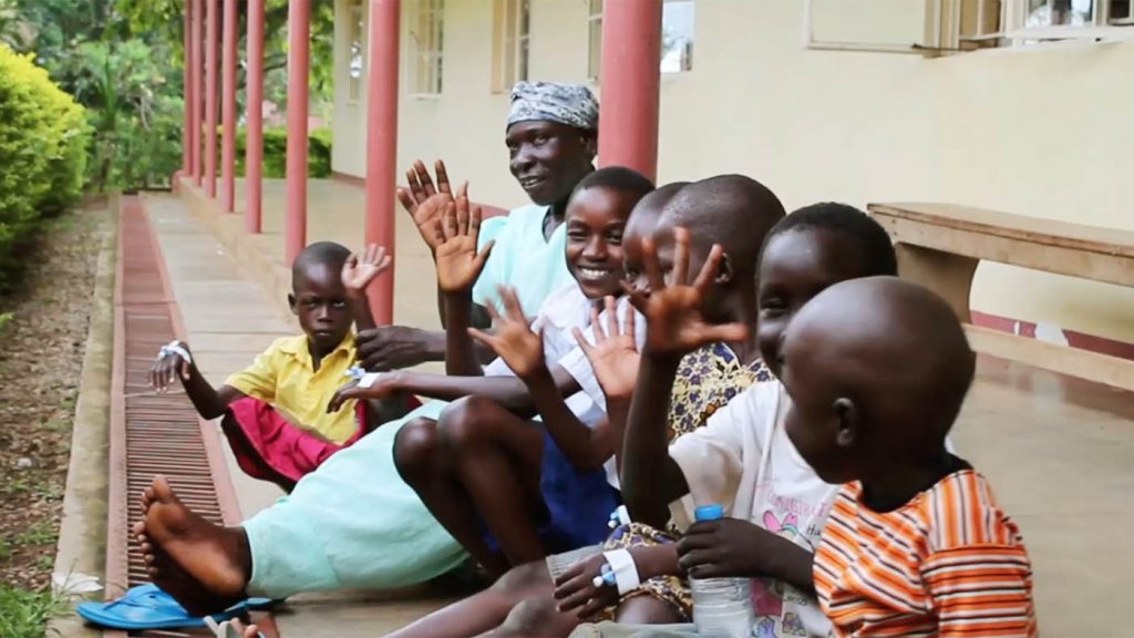 A group of children and a women sitting by an African railway station and waving to camera