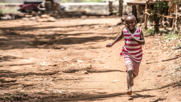 Asha runs down the road outside her home in Zanzibar days after a successful bilateral cataract operation.