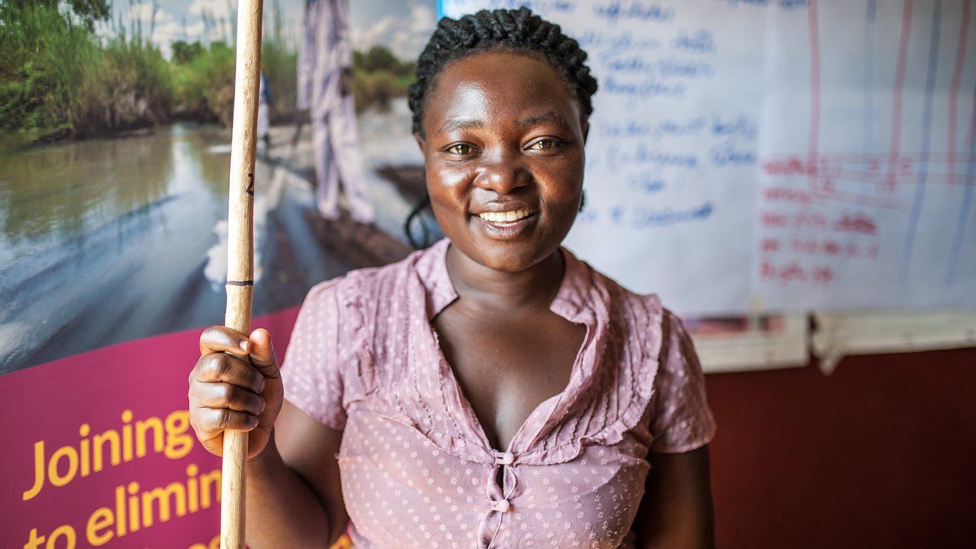 Una donna sta sorridendo e tiene un bastone per misurare le dosi di medicine da dare.