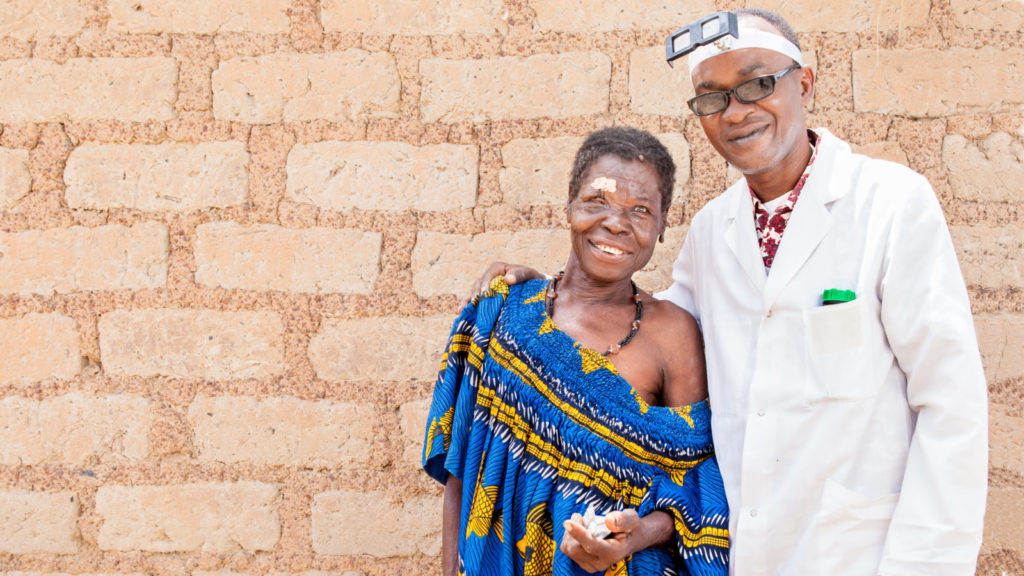 Diokoura standing with the trachoma surgeon, Modibo Sanogo, in Mali.
