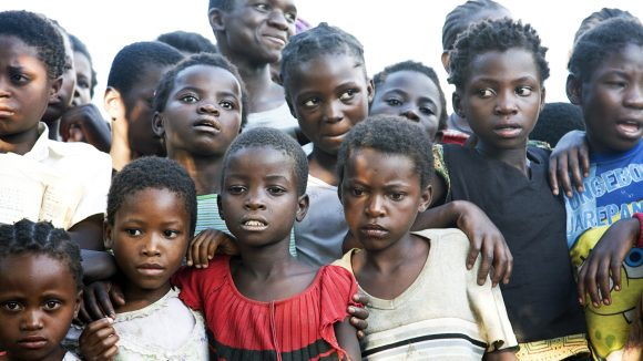A group of children standing, some have their arms over other children.