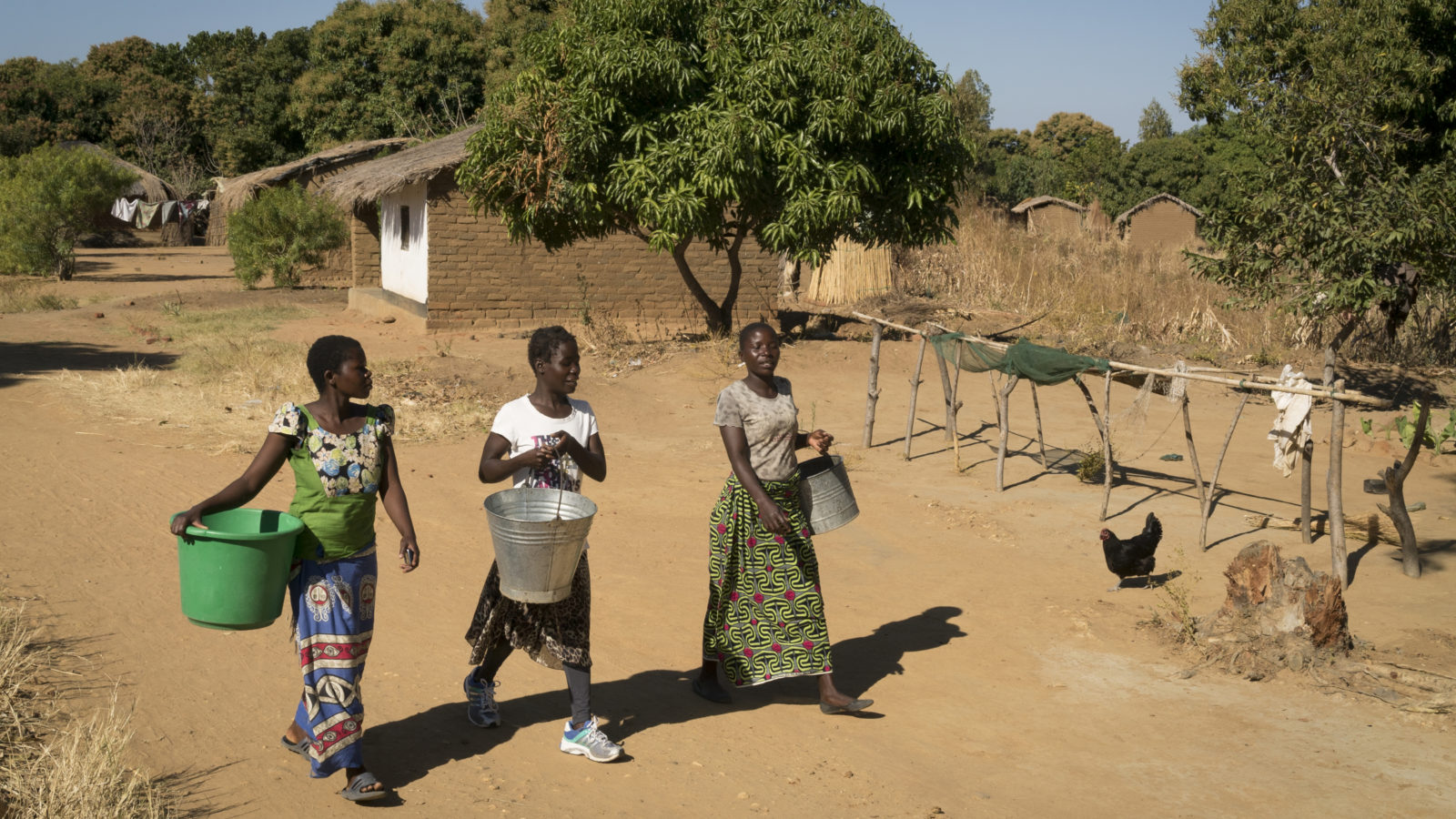 Taonere Banda, 20, (center) walks through the main street of her town to collect water with her childhood friends Zwani (right) and Tiyanjane (left) in Nkhotakota, Malawi.