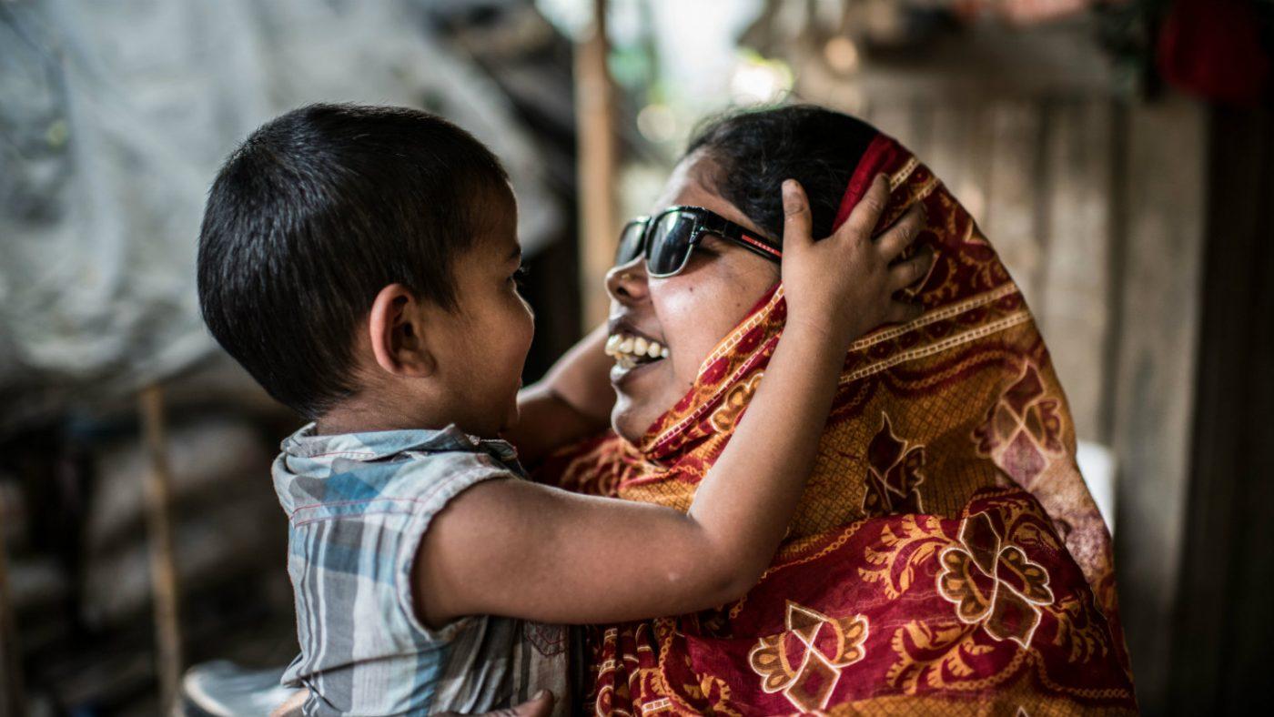 Un bambino tiene in mano la testa di una donna con degli occhiali da sole che sta sorridendo.