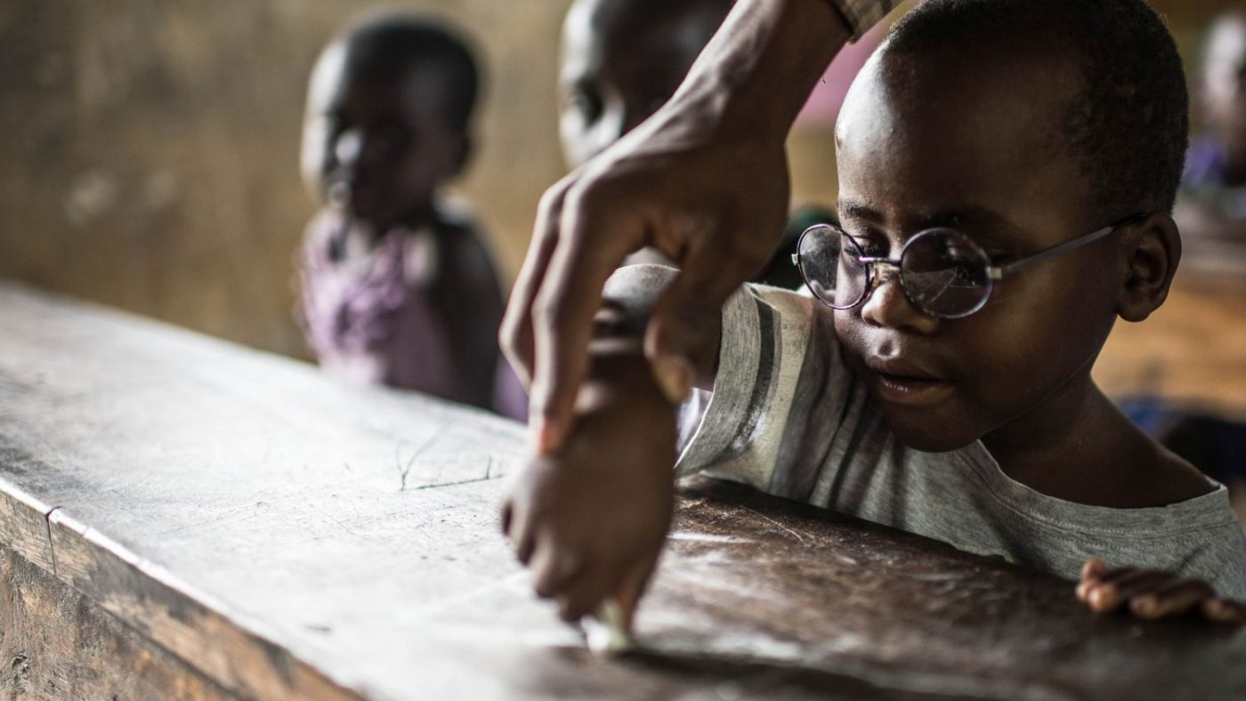 Una mano guida quella di un bambino mentre prova a scrivere con un gessetto su una tavola di legno