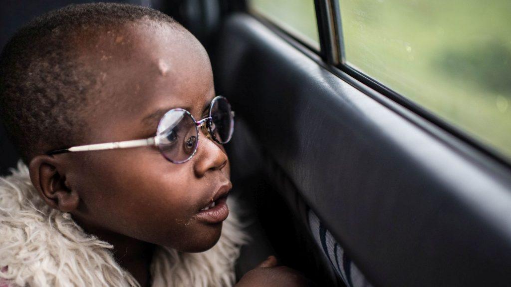 Un bambino con gli occhiali guarda fuori dal finestrino di un'auto