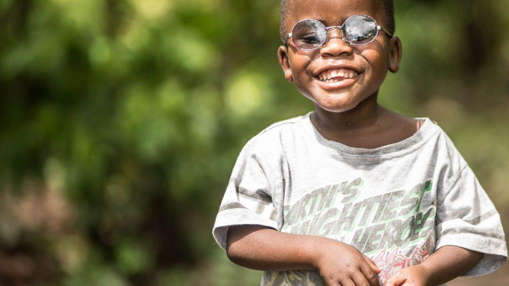 Un bambino con gli occhiali scuri sorride