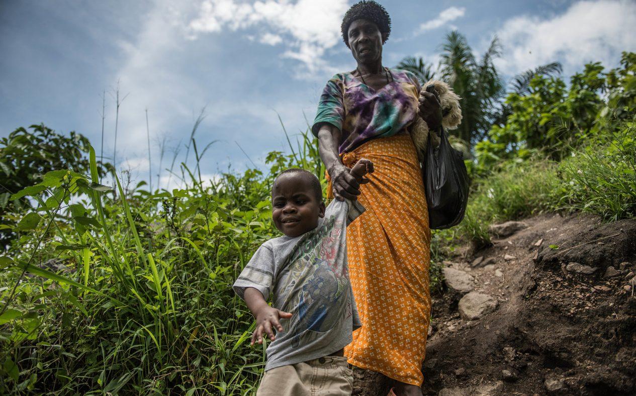 Una donna un bambino per mano che cammina davanti a lei lungo un sentiero sterrato