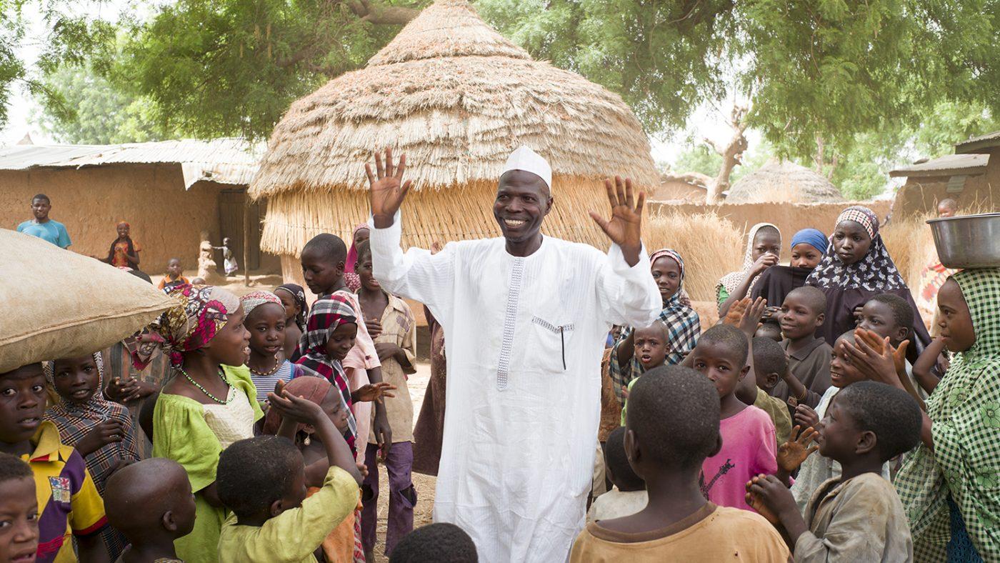 Un uomo sorridente vestito di bianco in un villaggio con capanne di paglia è circondato da bambini