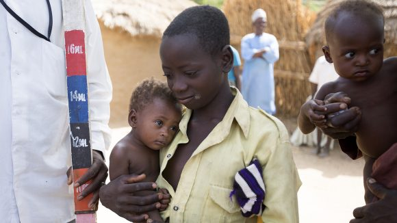 A boy and his baby brother wait to be given medication to treat NTDs in Nigeria.