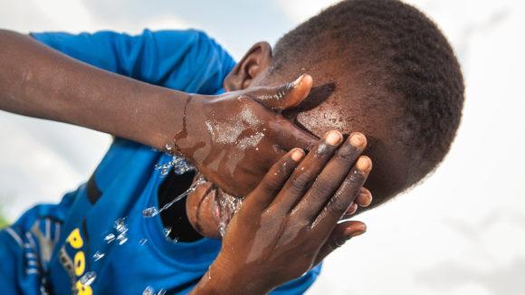 Un ragazzo si lava la faccia per proteggersi dall'infezione del tracoma.