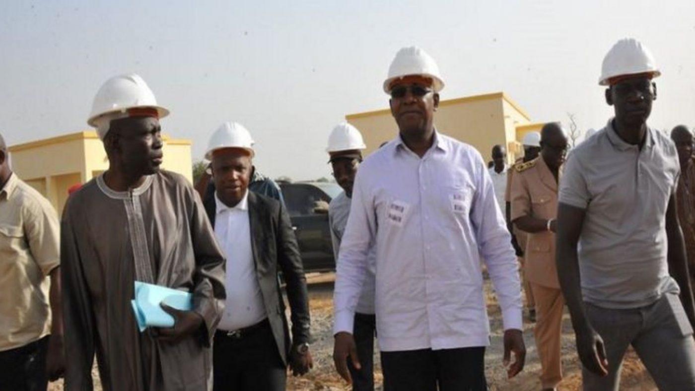Il Ministro dell'istruzione del Senegal è accampagnato da ispettori sul cantiere di una residenza per studenti, portano il casco di protezione