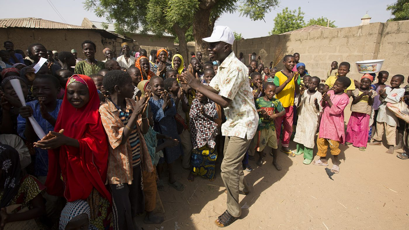 Ophthalmic nurse and lead surgeon, Aliyu A-Umar dances with children in Basansan, Kware.
