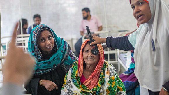 Una donna anziana sta guardando le dita del dottore in ospedale per verificare la sua vista