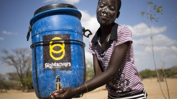 Una ragazzina si lava le mani sotto una tanica blu con il logo di Sightsavers