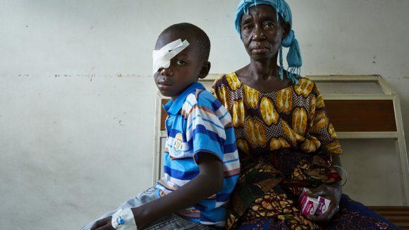 Una donna è seduta accanto a un bambino che ha una benda sull'occhio