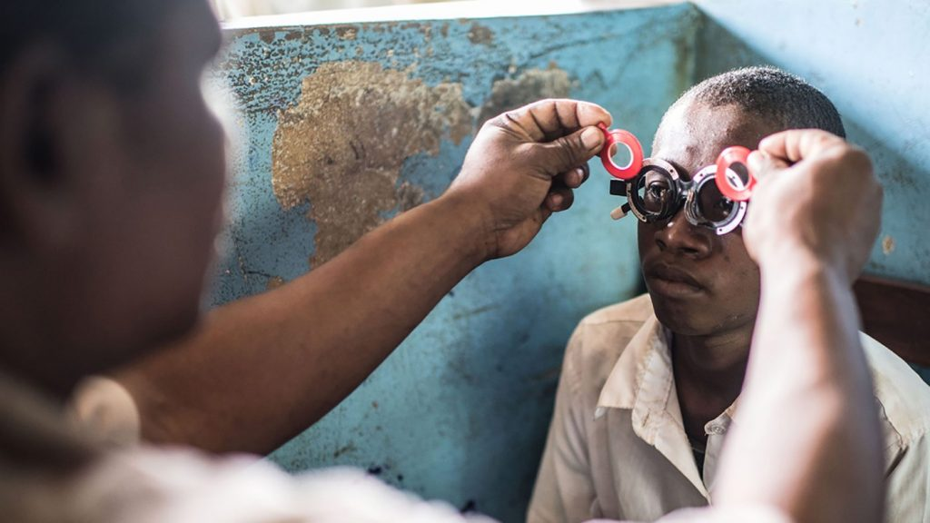 A boy has his eyes tested for refractive error.
