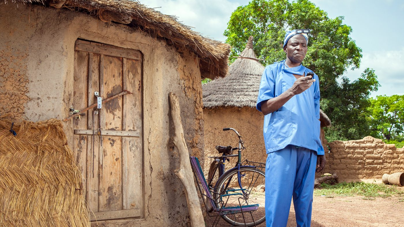 An eye health worker uses a mobile phone to record data.