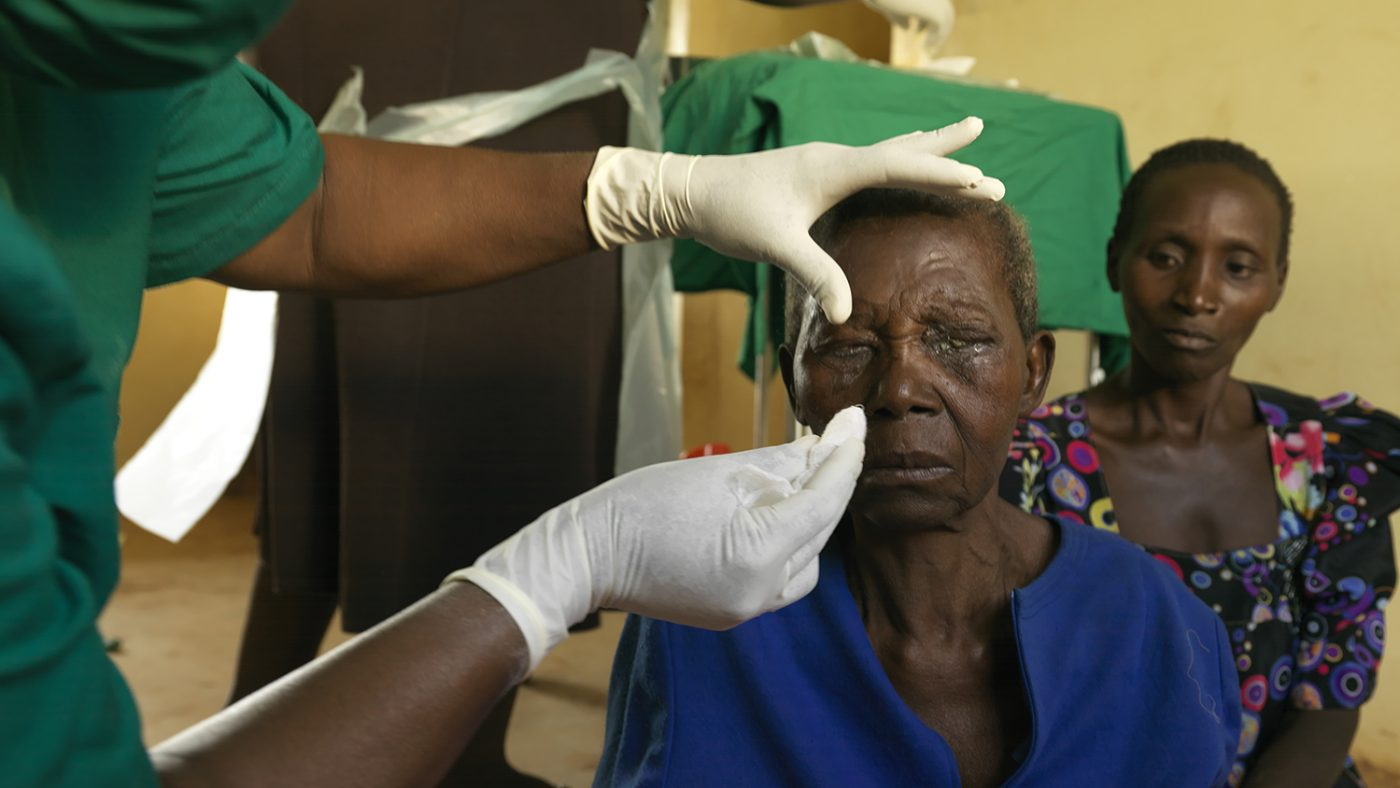 A health worker checks a woman's eyes for trachoma.