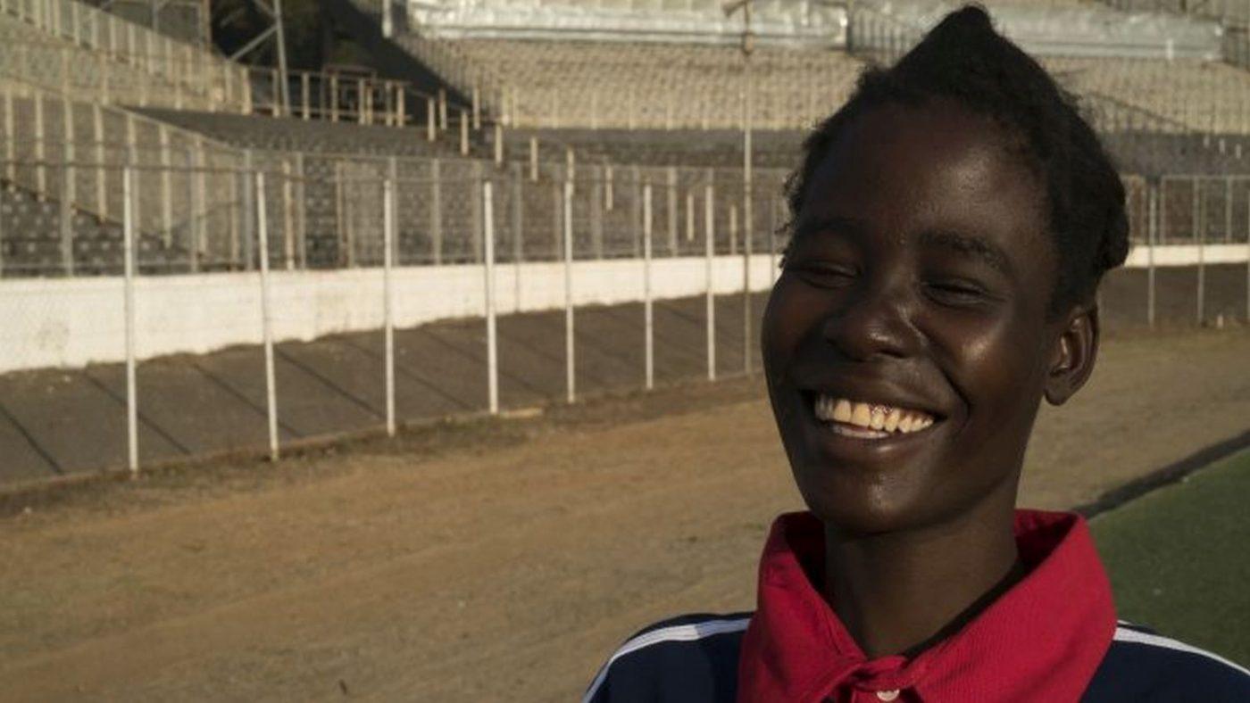 Una ragazza sorride con gli occhi chiusi al bordo di una pista di atletica