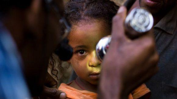 Una torcia illumina il viso di una bambina in primo piano