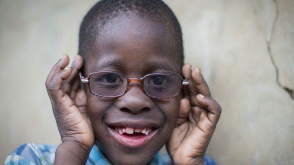 Un bambino in primo piano con le mani sugli occhiali da vista