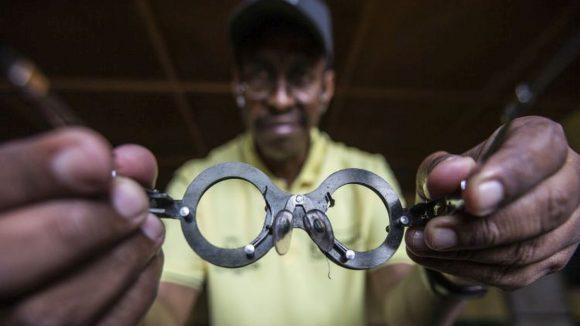 In primo piano un paio di occhiali tenuti in mano da un uomo sfuocato che guarda la macchina fotografica