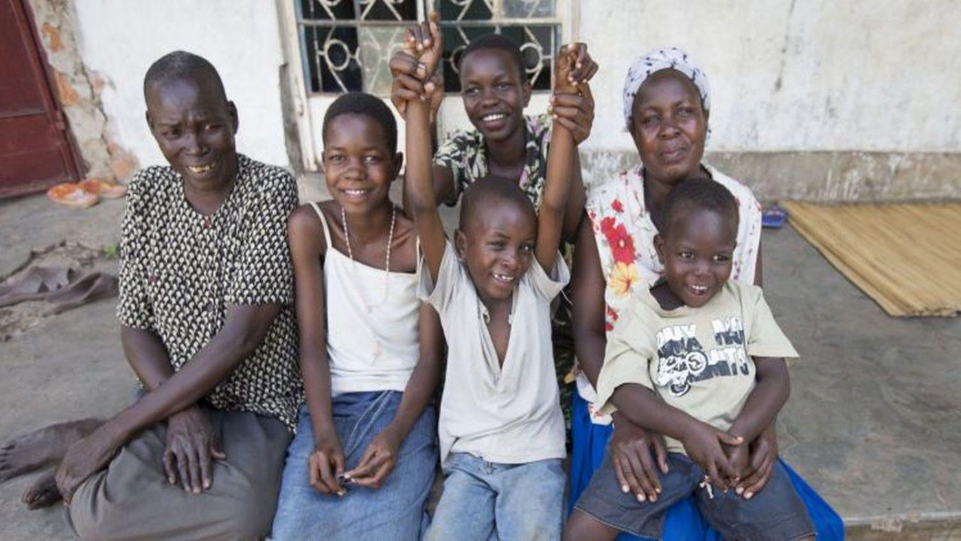 Sei persone sedute su un marciapiede, tutte con espressione allegra: un'anziana signora, due bambini, due ragazzine e una donna