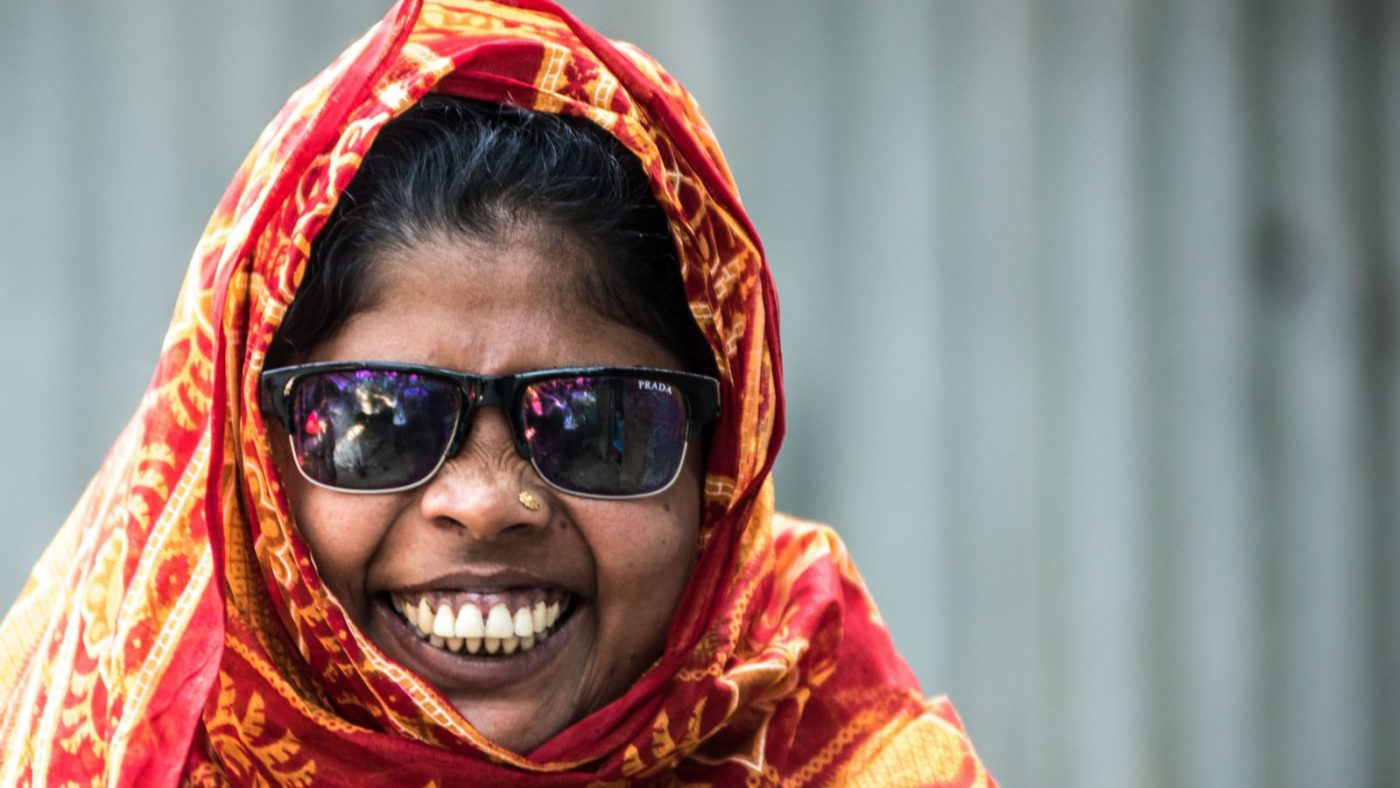 Smiling woman wearing sunglasses and orange headscarf.