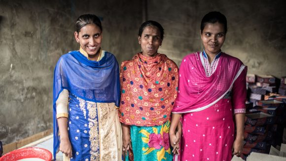 Three women wearing saris stand together smiling.
