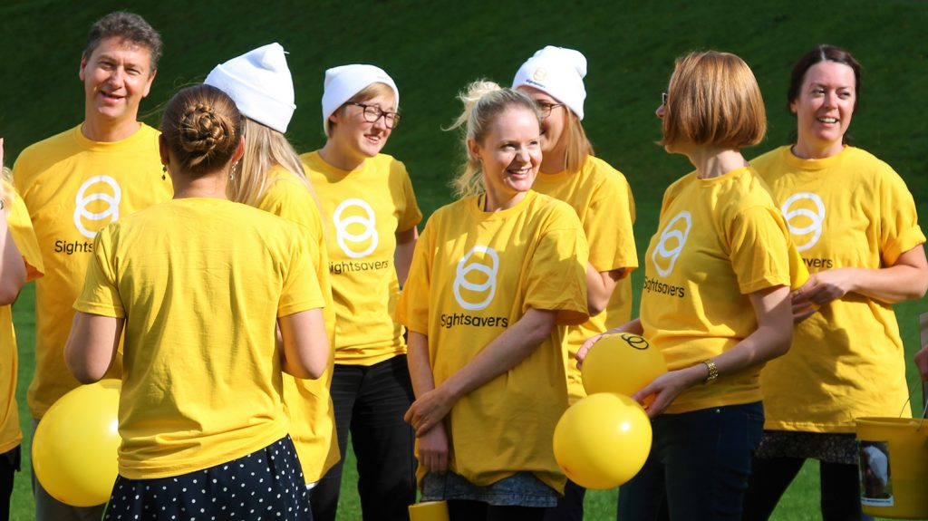 A group of males and females wearing yellow Sightsavers t-shirts. All are smiling.