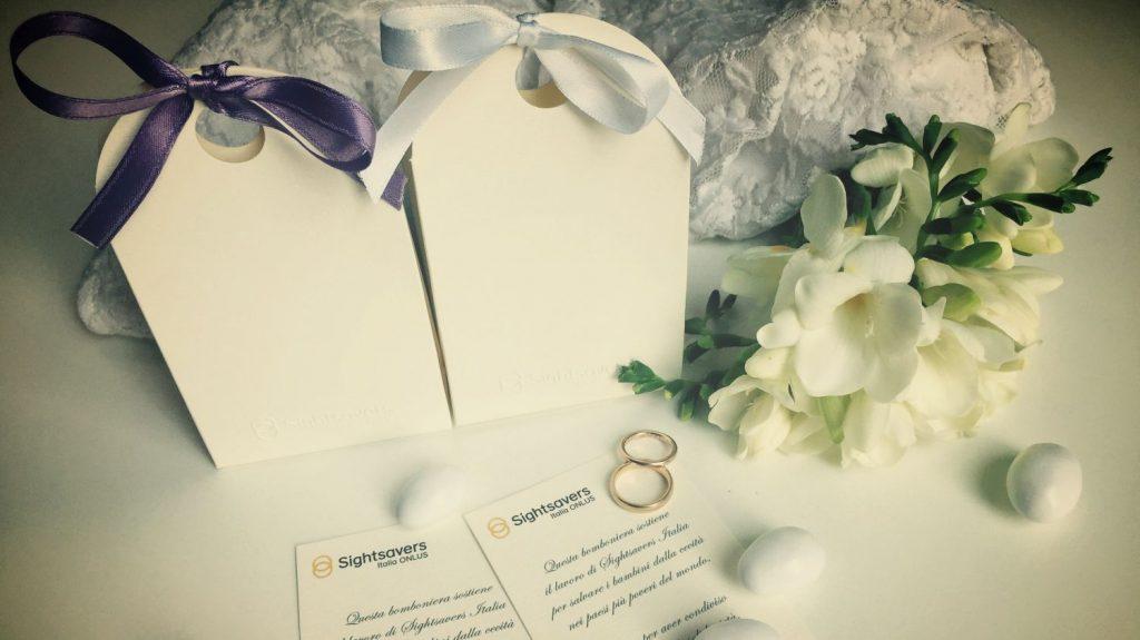 Su un tavolo sono presenti due scatoline due bigliettini due fedi e dei fiori.