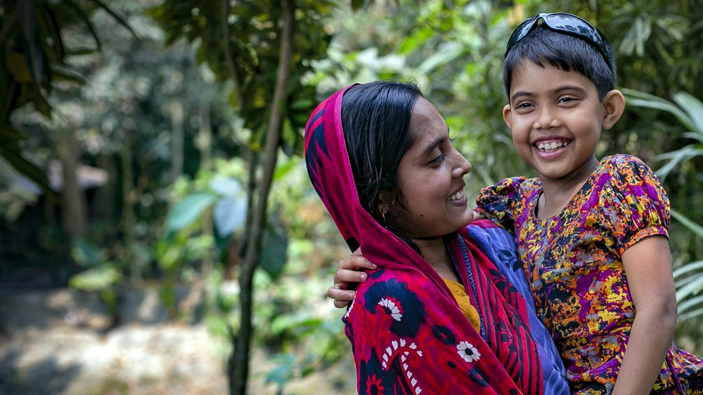 Aklima and her mother smile outside their home.