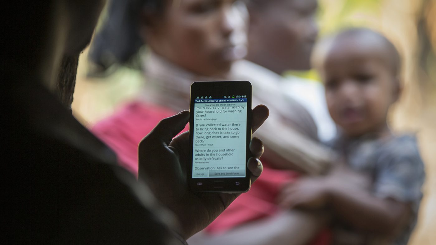 An eye health worker looks at his mobile phone.