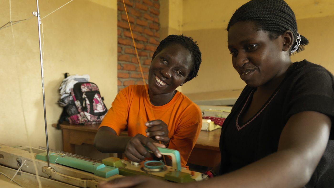 Una donna cieca sta sorridendo mentre lavora a maglia con un insegnante.