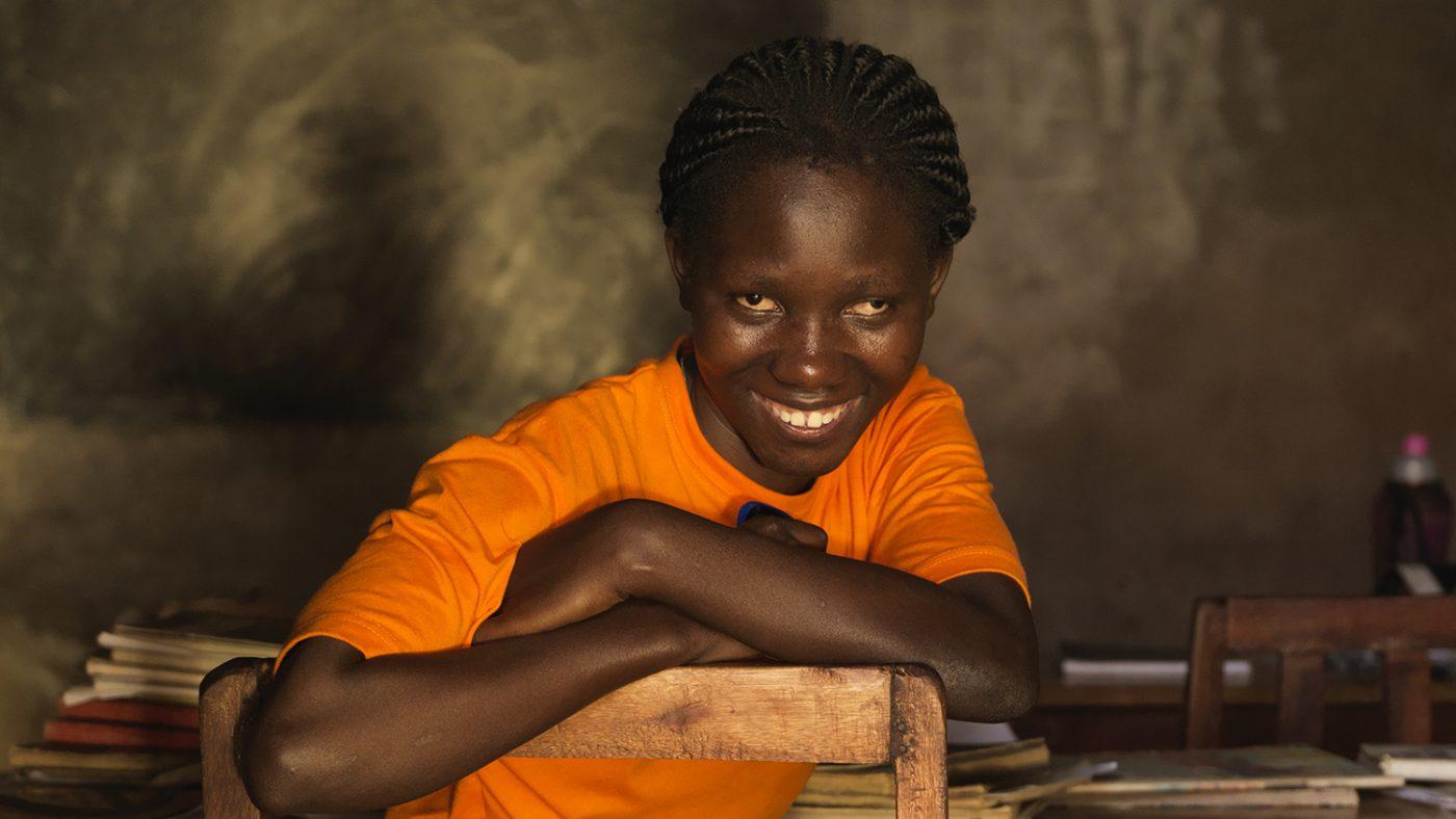 Una donna cieca sta seduta su una sedia e sorride guardando davanti a sè.
