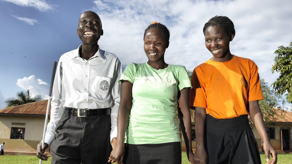 Un uomo e due donne stanno sorridendo.
