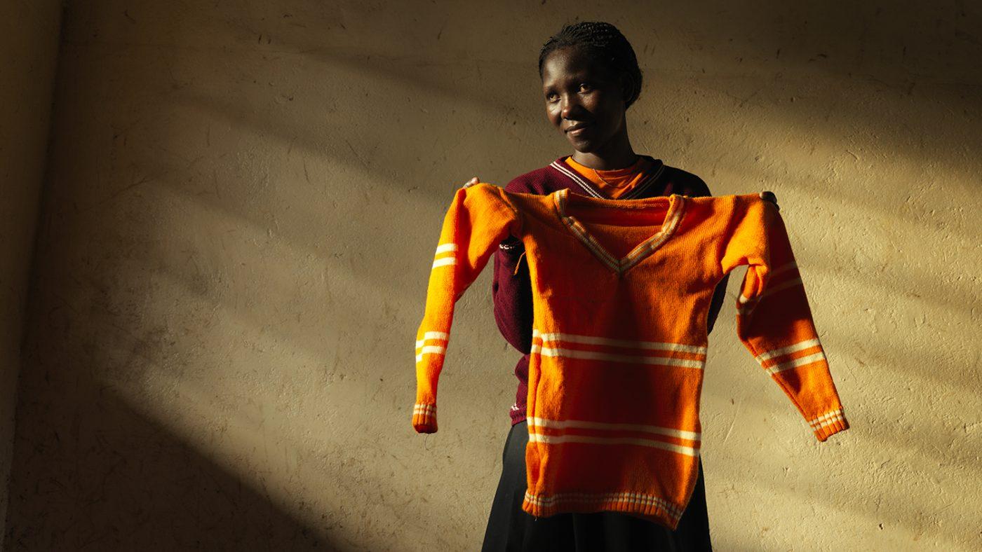 Una donna sta mostrando il maglione che ha cucito.
