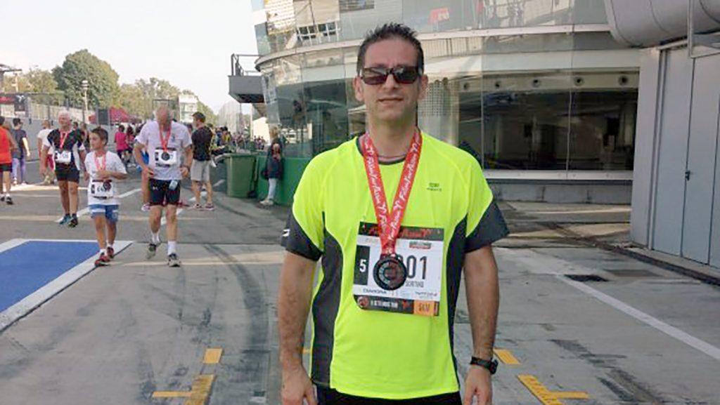 Un uomo in piedi con gli occhiali da sole e una maglia gialla e una pettorina da runner, porta una medaglia al petto