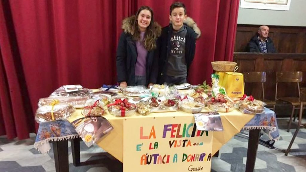 """Due ragazzini sono in piedi davanti a un tavolo pieno di torte in vendita e davanti attaccato al tavolo un cartellone con lo slogan """"La felicità è la vista...aiutaci a donarla. Grazie""""."""