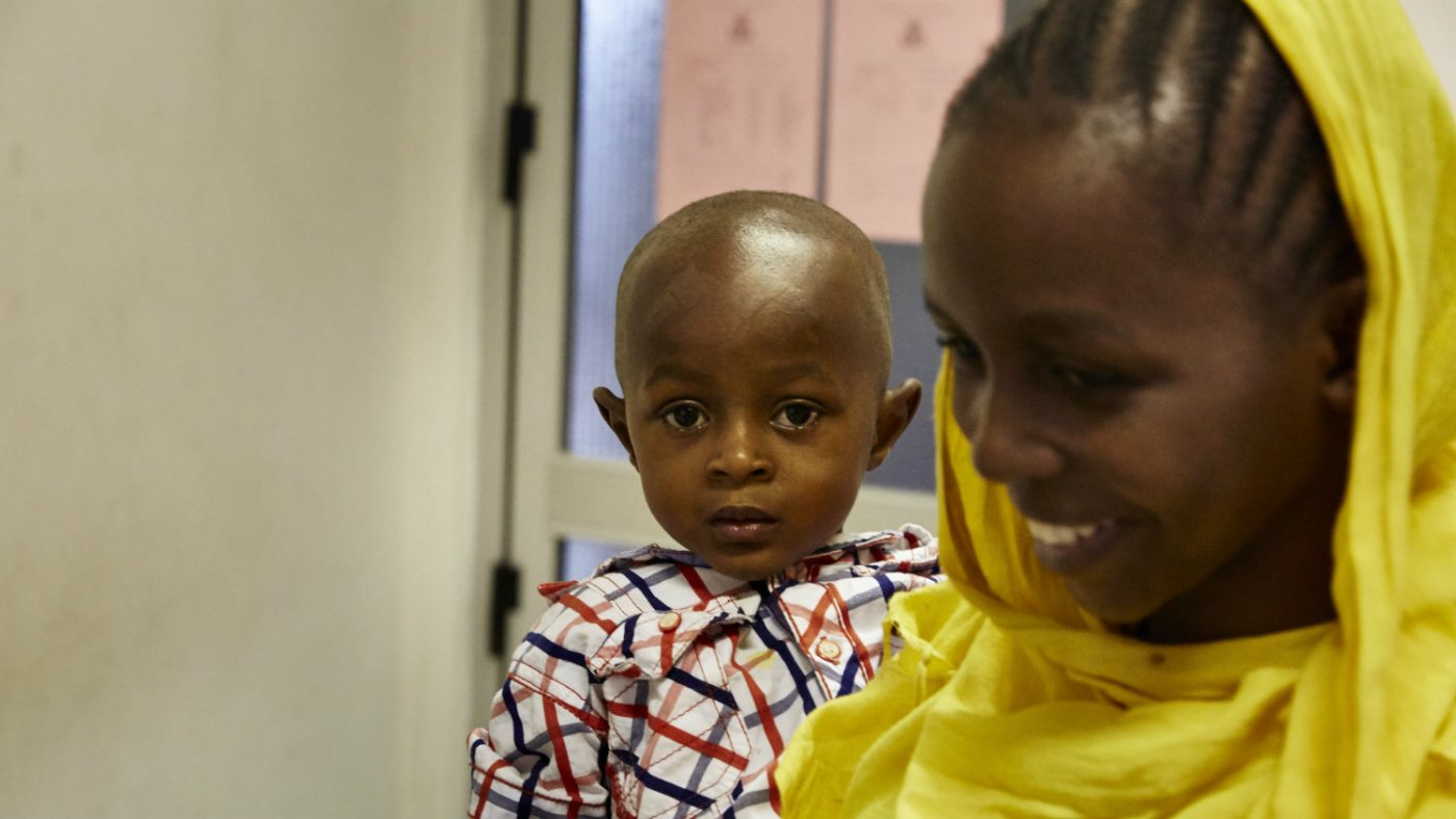 Baraka and his mother, smiling, in the hospital.