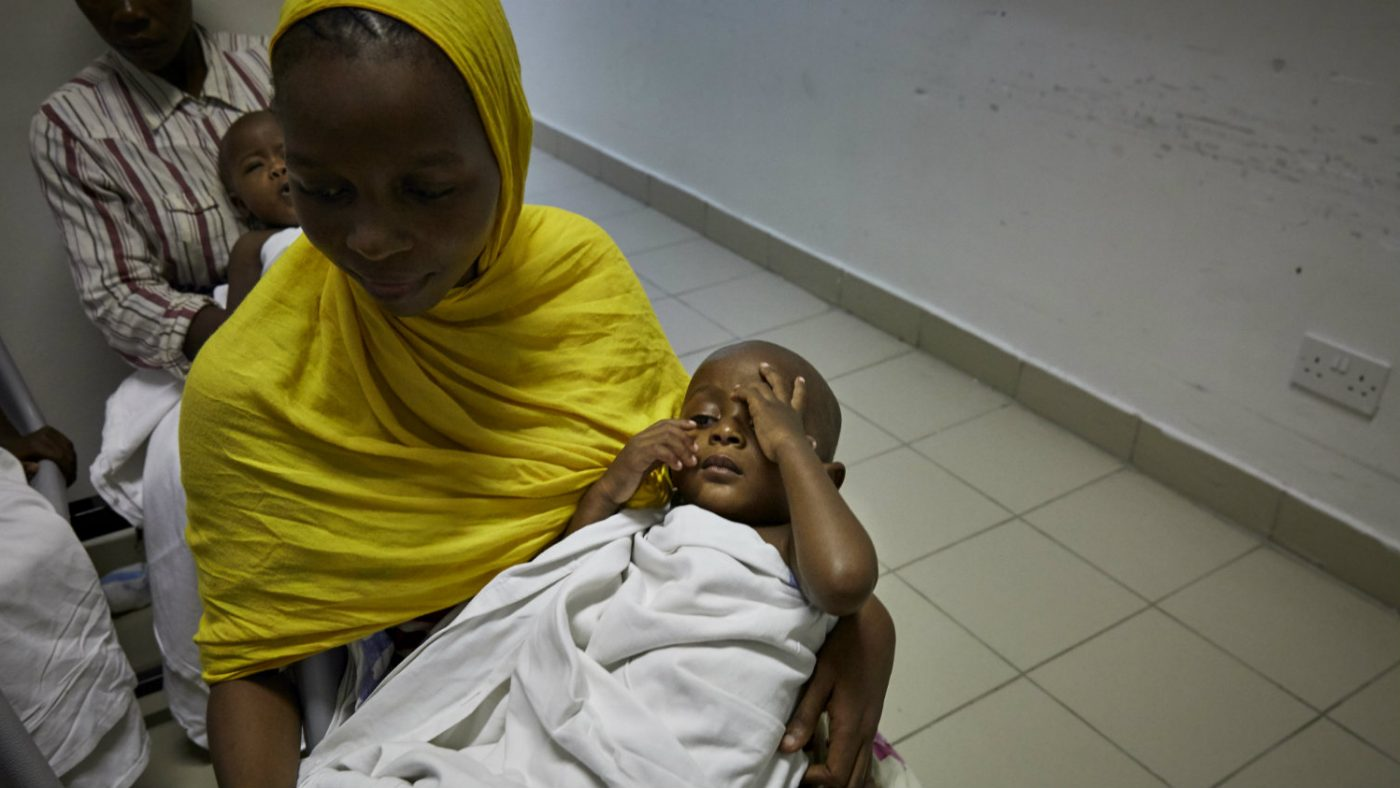 Baraka on hs mother's lap before the operation.