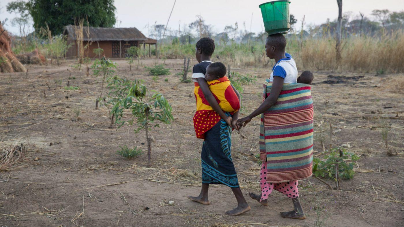 Laurinda is guided by a friend to collect water.